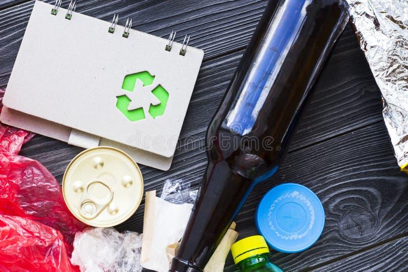 环保,生态和回收概念,回收标志、笔记薄和垃圾在黑暗的木背景 库存照片