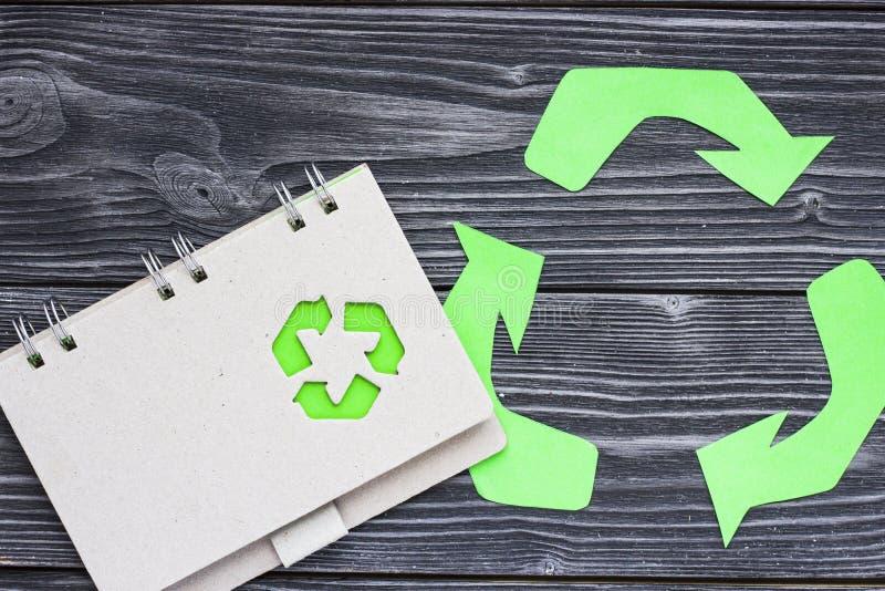 环保,生态和回收概念,回收标志、笔记薄和垃圾在黑暗的木背景 图库摄影