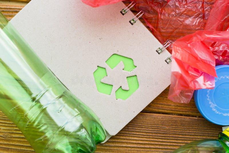 环保,生态和回收概念,回收标志、笔记薄和垃圾在黑暗的木背景 免版税库存图片