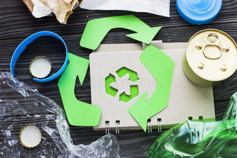环保,生态和回收概念,回收标志、笔记薄和垃圾在黑暗的木背景 库存图片
