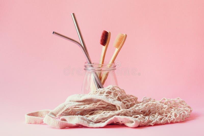 环境友好和塑料自由生活方式、可再用的金属秸杆,竹牙刷和白色串购物带来在粉红彩笔 库存图片