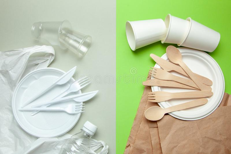 环境友好的一次性碗筷由竹木头和纸制成在绿色背景 塑料有害的盘和利器 免版税库存图片