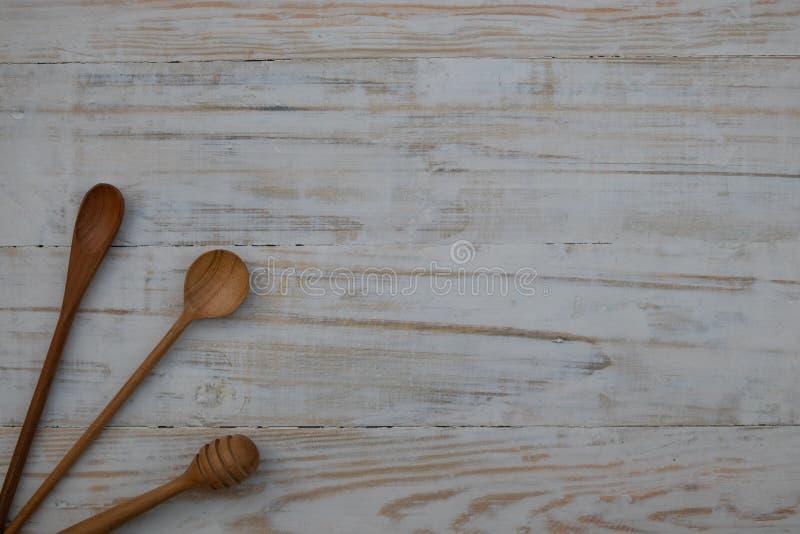 环境友好的木匙子和蜂蜜棍子在木桌背景 不伤环境的厨房用具舱内甲板放置与拷贝 图库摄影