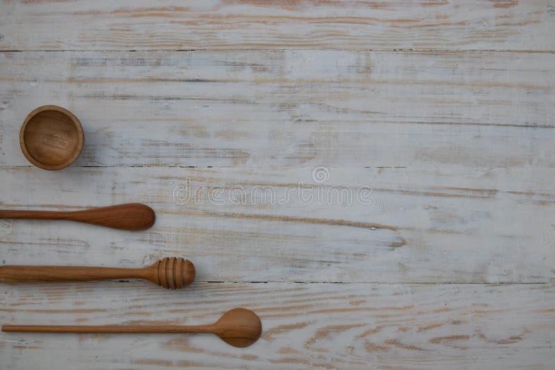 环境友好的木碗、匙子和蜂蜜棍子在木桌背景 不伤环境的厨房用具平的位置 图库摄影