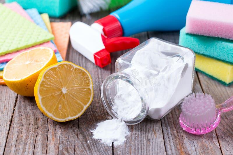 环境友好的自然擦净剂发面苏打、柠檬和布料在木桌上在手中 免版税库存照片