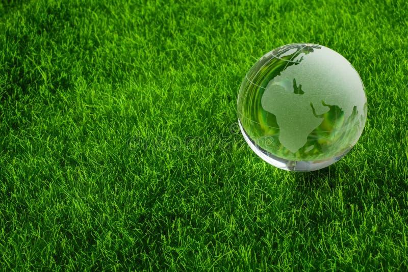 环境概念,在草的玻璃地球 免版税库存照片