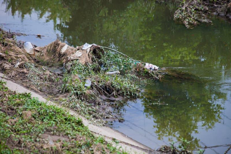 环境污染、塑料、袋子、瓶和垃圾在河 免版税库存图片