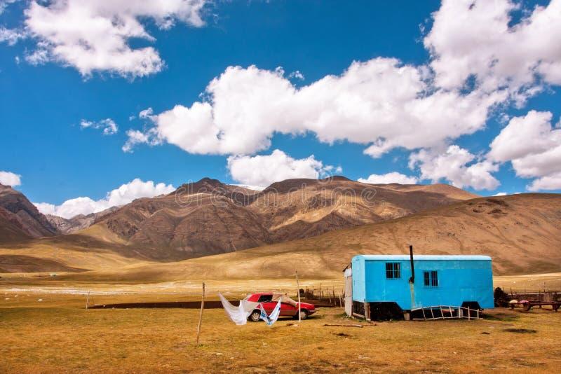 环境美化与农夫` s拖车和汽车在一个谷在吉尔吉斯斯坦的山之间 免版税库存照片