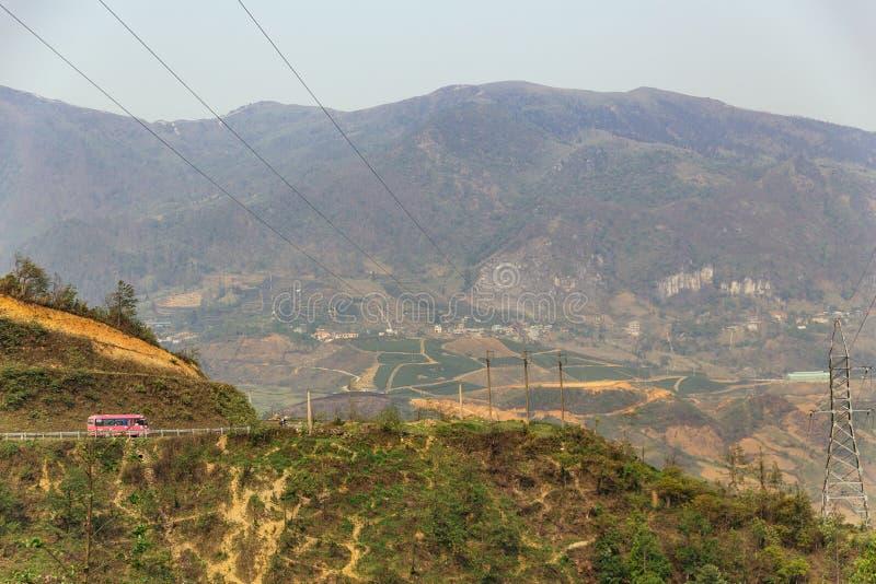 环境美化与电岗位和树与桃红色颜色公共汽车在左边在夏天在Sa Pa,越南 免版税库存照片