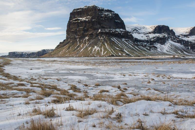 环境美化与积雪的草和Lomagnupur山,冰岛 库存照片