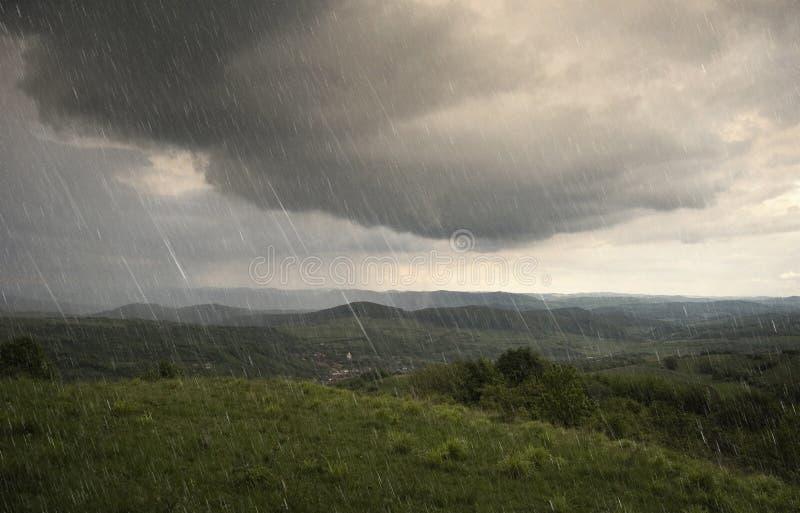 环境美化与雨和在小山的严重的云彩 免版税库存图片