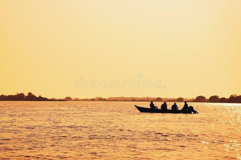 环境美化在一条小船的日落有钓鱼在潘塔纳尔湿地的渔夫的 库存照片