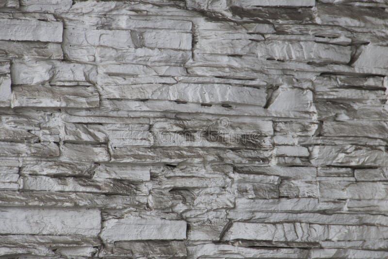 现代与水泥的样式设计装饰参差不齐的破裂的真正的石墙表面的样式灰色颜色 免版税库存照片