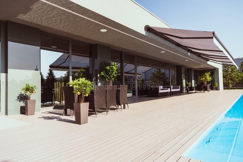 现代乡间别墅游泳场和门廊有小的树椅子的 图库摄影