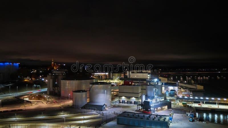 现代五谷终端在晚上 电梯金属坦克  五谷干燥复合体建筑 商业五谷或种子 免版税库存图片