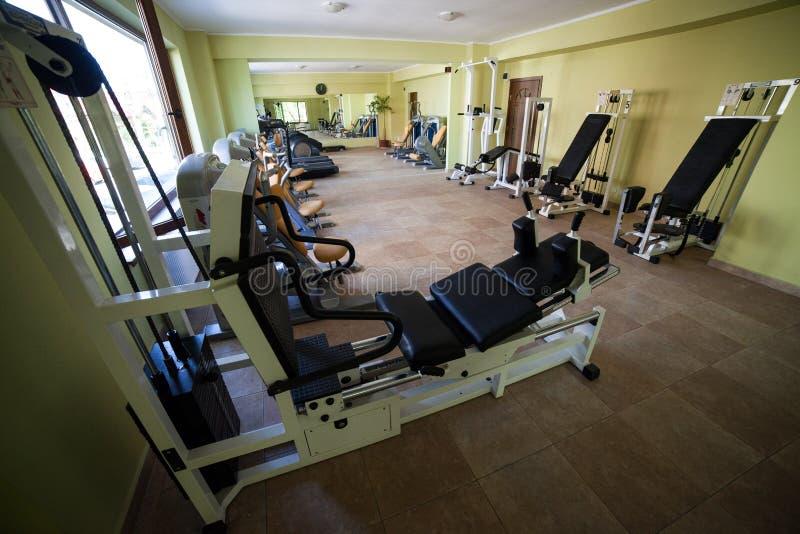 现代健身房内部用各种各样的设备 免版税库存图片