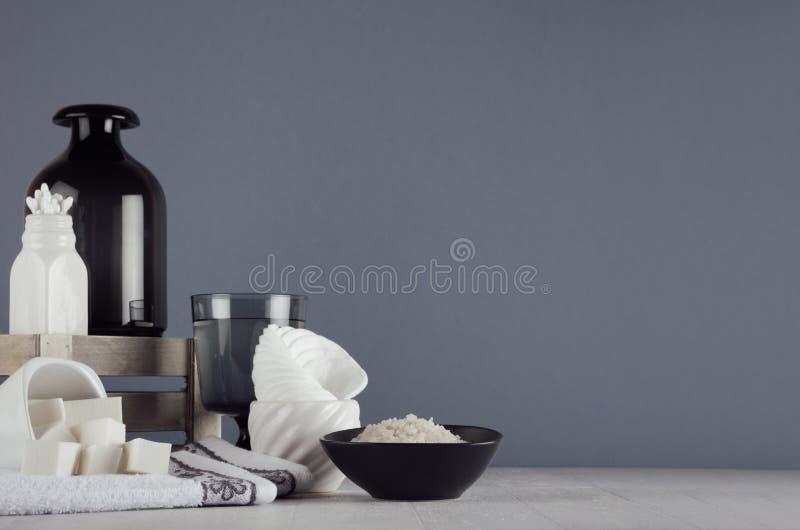 现代典雅的卫生间装饰-在白色陶瓷碗和墨镜花瓶的化妆用品辅助部件在白色木板,灰色墙壁 免版税库存照片