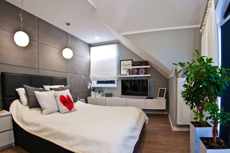 现代卧室内部在广角顶楼的屋子里 免版税图库摄影