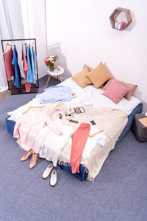 现代卧室内部大角度看法有挂衣架的有很多各种各样的女性衣物和构成供应 库存图片