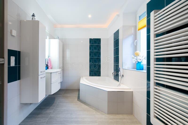 现代卫生间-光滑的白色和蓝色瓦片-浴缸、水槽和楼板暖气水平的射击 免版税库存照片