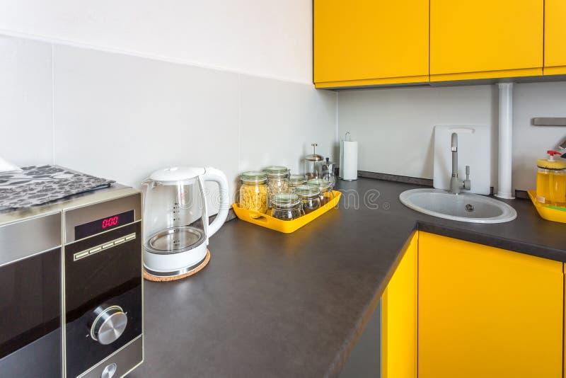 现代厨房的内部顶楼平的公寓的在与黄色颜色的minimalistic样式 图库摄影