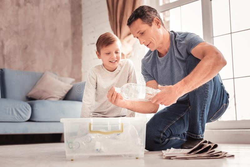 现代告诉父亲佩带的牛仔裤他的关于塑料的儿子 库存照片