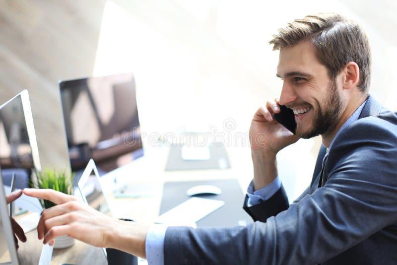 现代商人分析数据使用计算机和谈话在电话,当坐在办公室时 库存图片