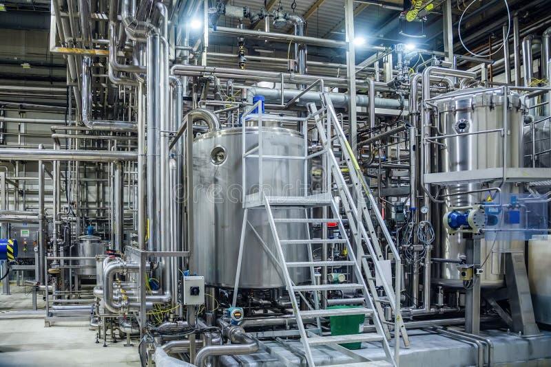 现代啤酒厂内部 滤清大桶、管道、阀门和啤酒生产线的其他设备 免版税库存照片