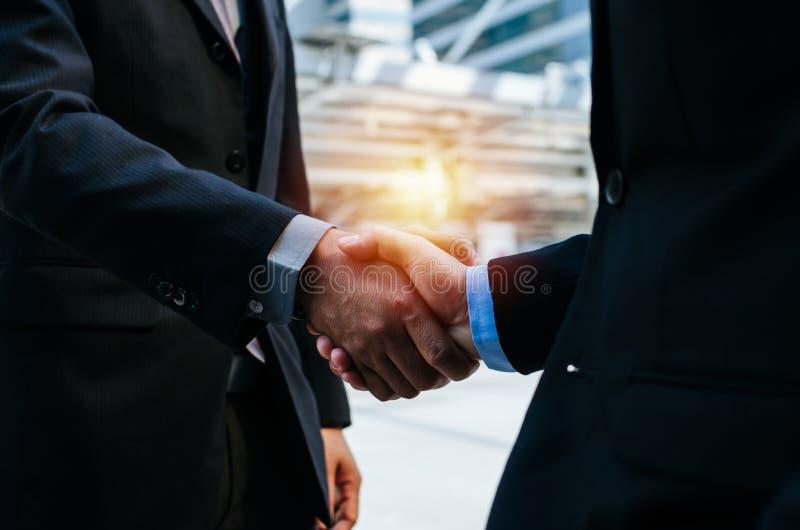 现代城市新工程合同会期间,两位年轻商人与合伙人握手 免版税库存照片
