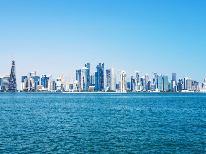 现代多哈市地平线都市风景与摩天大楼和江边的在好日子 免版税图库摄影