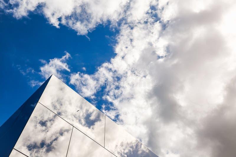 现代大厦外部设计,玻璃门面 鸟和多云天空的反射在玻璃 都市的背景 地平线建筑学 免版税库存图片