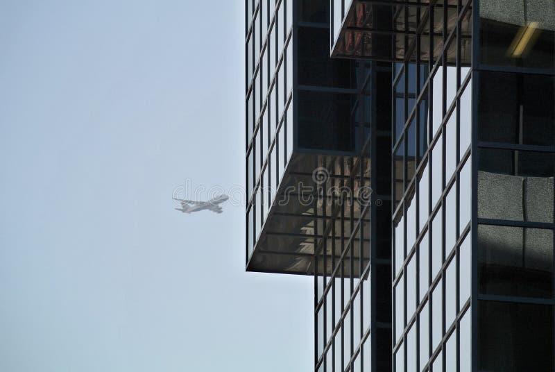 现代大厦玻璃门面在天空的细节和飞机在背景中 免版税库存照片