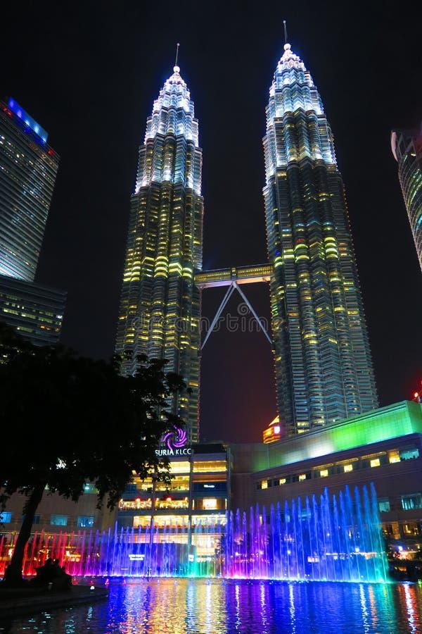 现代天然碱双塔吉隆坡马来西亚在与五颜六色的喷泉的夜之前 免版税库存图片