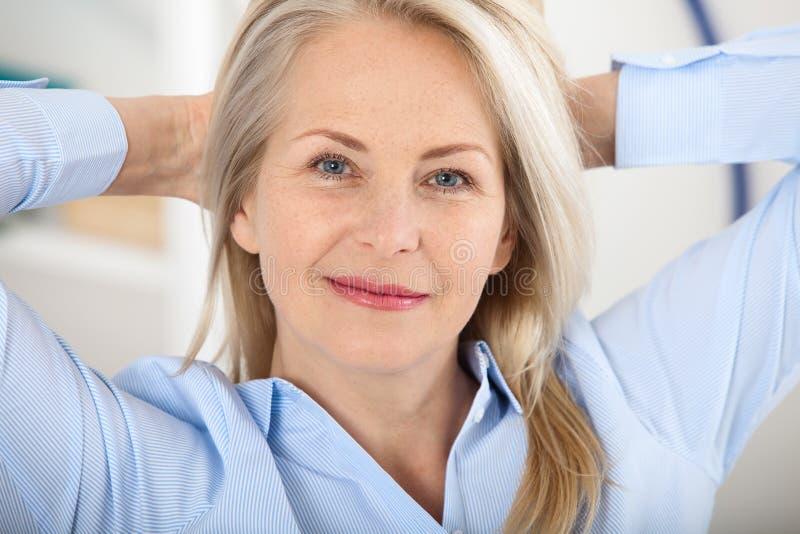 现代女实业家 美好的中部变老了看与微笑的妇女照相机,当选址在办公室时 库存照片