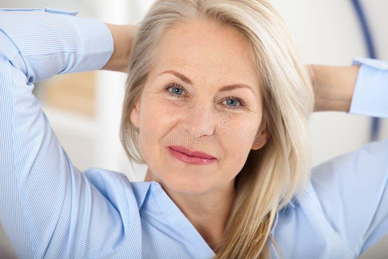 现代女实业家 美好的中部变老了看与微笑的妇女照相机,当选址在办公室时 免版税库存照片