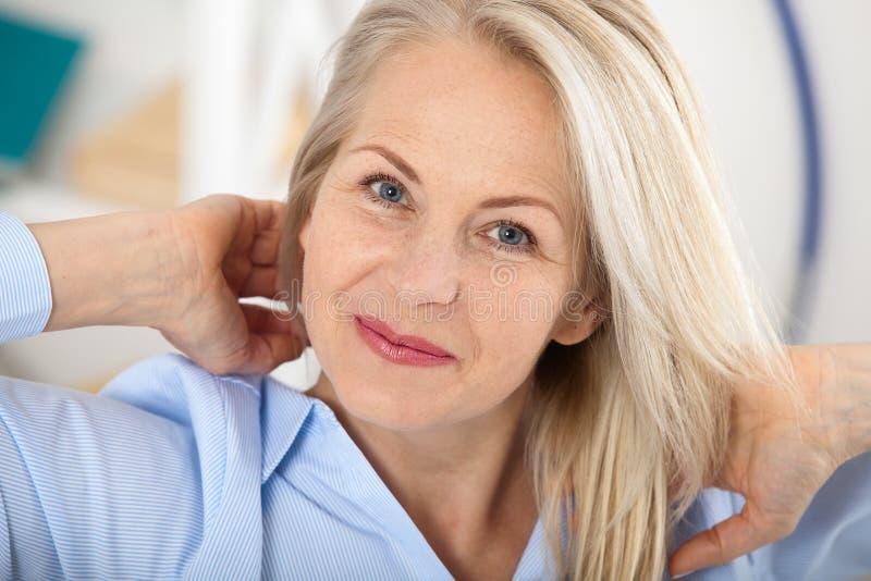 现代女实业家 美好的中部变老了看与微笑的妇女照相机,当选址在办公室时 图库摄影