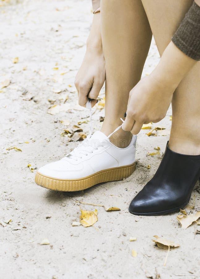 现代妇女更换她的运动鞋的在公园,女性脚鞋子 免版税图库摄影