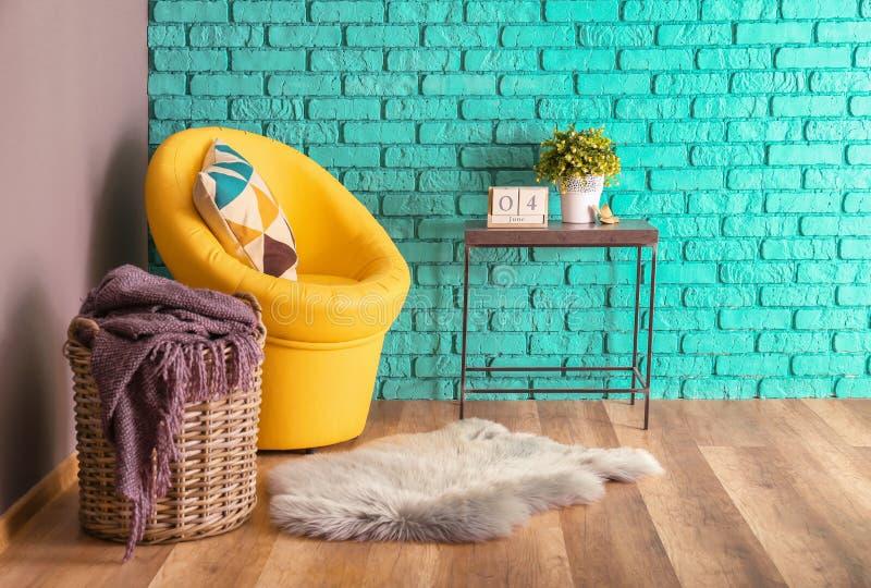 现代室内部有篮子、扶手椅子和室内植物的在颜色墙壁附近的桌上 库存图片