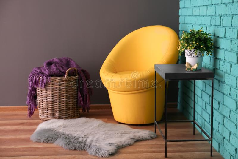 现代室内部有篮子、扶手椅子和室内植物的在颜色墙壁附近的桌上 免版税库存图片