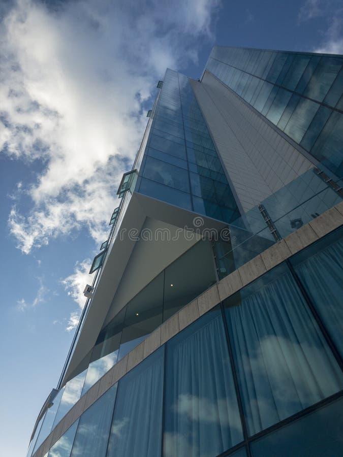 现代宫殿建筑学,反射性窗口,玻璃宫殿 在大厦的窗口里反映的天空 在天空,角落的云彩 库存图片