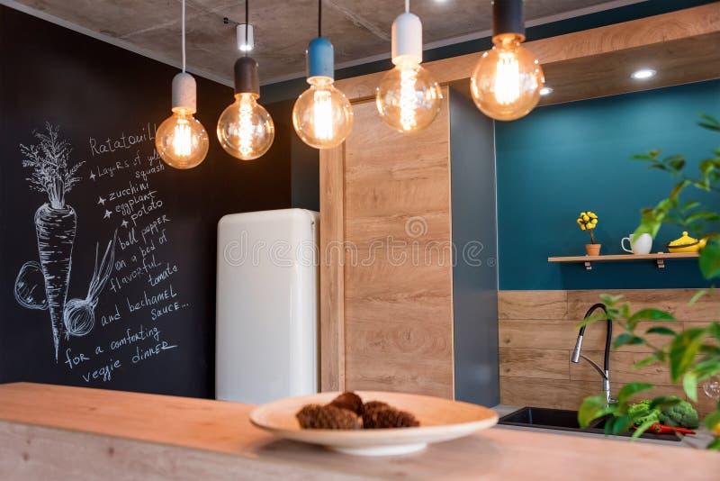 现代家具在豪华厨房里 在顶楼公寓的最低纲领派斯堪的纳维亚内部与木家具,灯 免版税库存照片