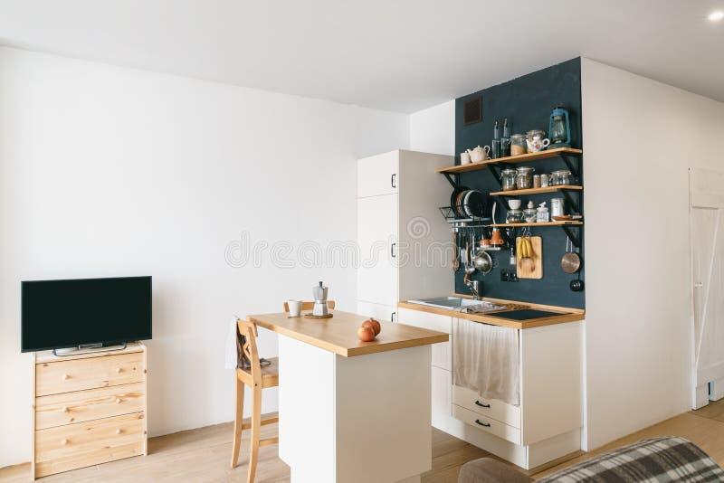 现代家庭厨房设计顶楼和土气样式的 有架子的,盘子,瓶子,杯子黑墙壁 冰箱,用餐tabl 库存照片