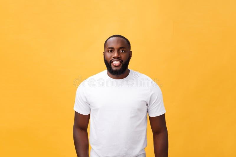 现代年轻黑人微笑的站立的被隔绝的黄色背景的画象 免版税库存图片