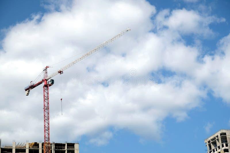 现代建筑大厦的大卷扬的塔吊和上面部分在蓝天的一个城市与云彩 库存照片