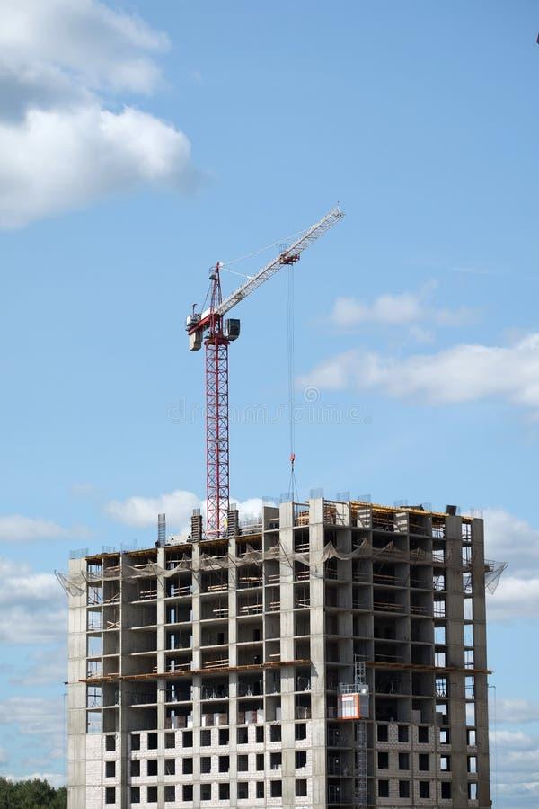 现代建筑大厦的大卷扬的塔吊和上面部分在蓝天的一个城市与云彩 免版税库存图片
