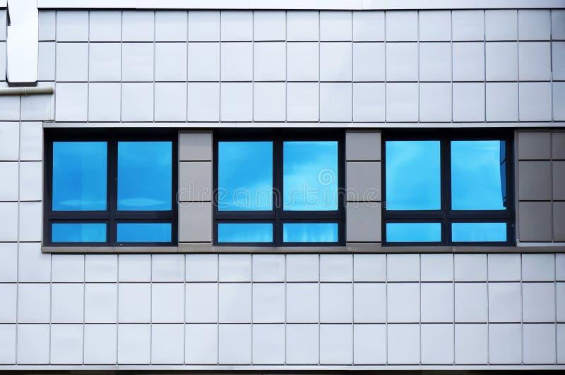 现代建筑的立面 蓝天在窗户中的反射 免版税图库摄影