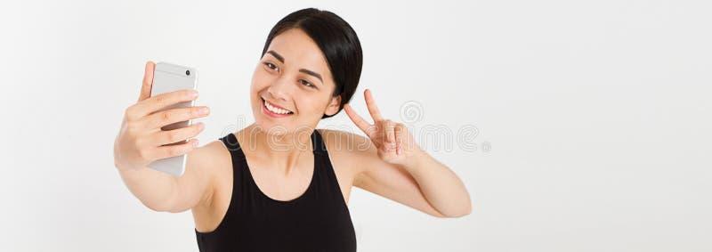 现代微笑逗人喜爱的女孩做selfie和展示两手指和平标志 库存照片