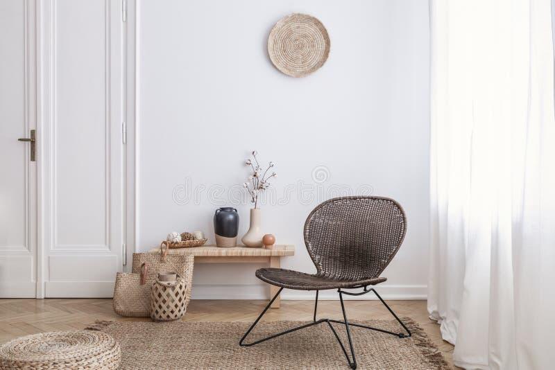 现代扶手椅子和蒲团在棕色地毯在白色公寓内部与门 实际照片 免版税库存照片