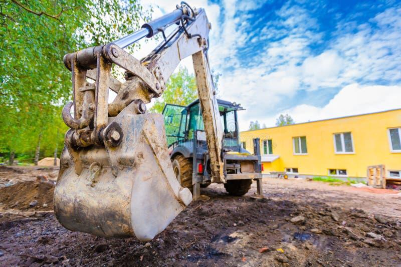 现代挖掘机进行在建造场所的挖掘工作 一个挖掘机的桶的正面图开掘的地面 免版税库存图片