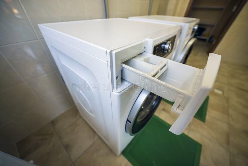 现代新的工业洗衣机在干净的铺磁砖的卫生间或洗衣房里橡胶绝缘材料席子的 图库摄影